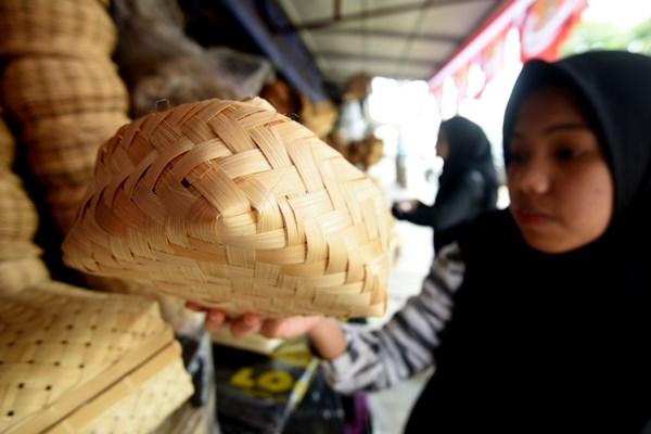 Seorang calon pembeli mencermati besek bambu yang dijual di sebuah kios di Jalan Jatinegara Barat, Jakarta Timur, Sabtu (10/9/2019). Sejumlah pedagang mulai menjual besek yang terbuat dari bambu untuk membungkus daging kurban saat Idul Adha. - ANTARA/Adnan Nanda