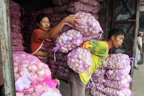 Buruh angkut menggendong bawang putih kemasan karung di Pasar Legi, Solo, Selasa (18/4). - JIBI/Sunaryo Haryo Bayu