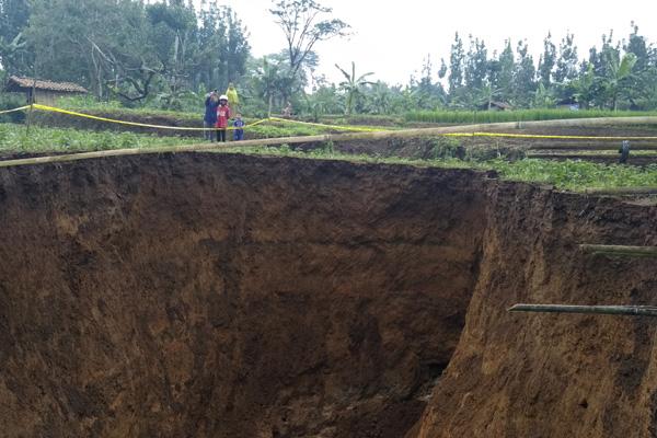 Warga menyaksikan lubang raksasa di area persawahan di Desa Sukamaju, Kadudampit, Kabupaten Sukabumi, Jawa Barat, Minggu (28/4/2019). Penyebab terjadinya lubang raksasa yang memiliki diameter sekitar 16 meter dengan kedalaman 12 meter tersebut belum diketahui. - Antara/ Aditya Aulia