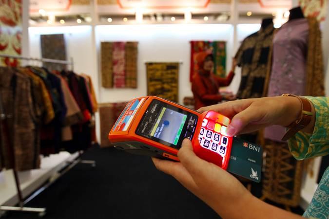 Pengunjung melakukan transaksi saat berbelanja batik di booth BNI saat acara Gelar Batik Nusantara di Jakarta, Rabu (8/5/2019). - Bisnis/Abdullah Azzam
