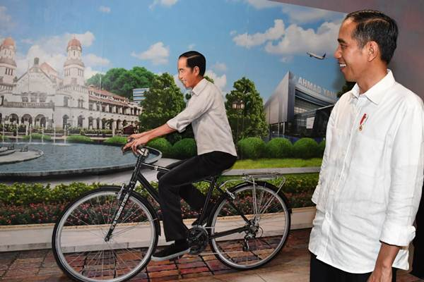 Presiden Joko Widodo (kanan) mengamati replika Joko Widodo naik sepeda, di sela-sela peresmian Terminal Baru Bandara Internasional Ahmad Yani, di Semarang, Kamis (7/6/2018). - Biro Pers Setpres/Laily Rachev
