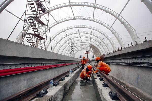 Pekerja menyelesaikan proyek pembangunan Light Rail Transit (LRT) di Jakarta, Senin (14/1/2019). - Bisnis/Abdullah Azzam