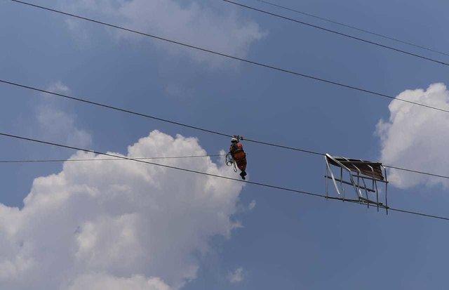 Tim PDKB TT Kalbar bergelantungan di tower transmisi 150 kV guna bersihkan plat seng rumah warga yang menempel. - Istimewa