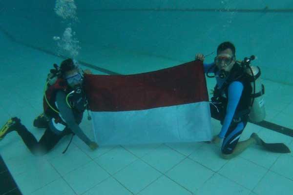 Bupati Kabupaten Batang Wihaji saat mengibarkan Bendera Merah Putih dibawah air - istimewa)