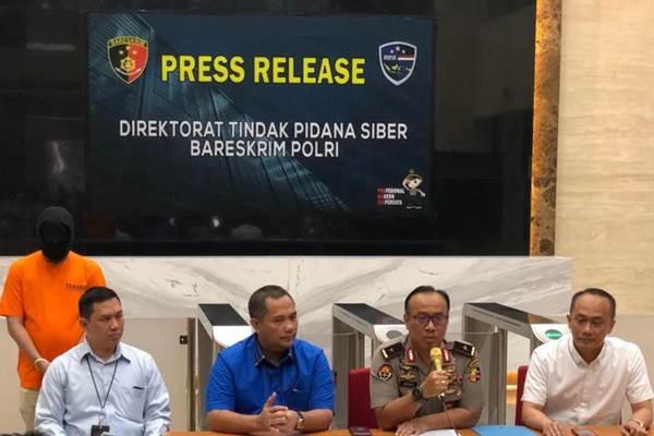Konferensi pers kasus penjualan data nasabah dan data kependudukan, tersangka C berdiri di belakang menggunakan baju tahanan dan penutup wajah - Bisnis/Sholahuddin Al Ayyubi