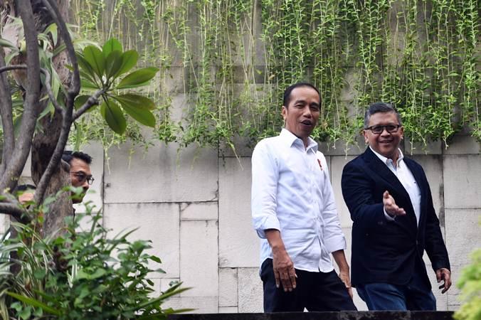 Presiden terpilih periode 2019-2024 Joko Widodo (kiri) bersama Sekjen PDIP Hasto Kristiyanto berjalan memasuki lokasi pertemuan dengan Tim Kampanye Nasional (TKN) Jokowi-Maruf Amin, di Jakarta, Jumat (26/7/2019). Agenda pertemuan membahas pembubaran TKN. - ANTARA/Akbar Nugroho Gumay