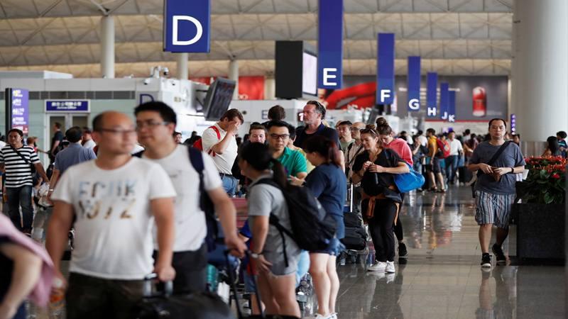 Penumpang mengantre ketika bandara dibuka kembali sehari setelah penerbangan dihentikan karena protes, di Bandara Internasional Hong Kong, Cina 13 Agustus 2019. - Reuters