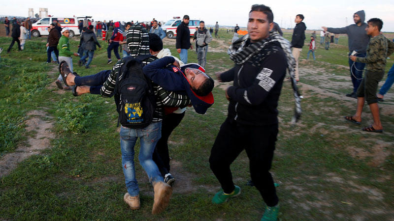 Seorang pengunjuk rasa dievakuasi saat aksi demo di Jalur Gaza Jumat 22 Februari 2019 petang waktu setempat. - Reuters/Mohammed Salem