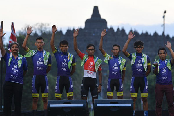 Tim PGN Road Cycling dan ofisial melakukan sesi foto dalam pembukaan Tour d'Indonesia 2019 di kompleks Candi Borobudur, Magelang, Jawa Tengah, Minggu (18/8/2019). - Antara/Sigid Kurniawan