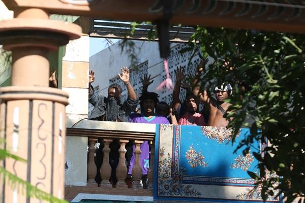 Sejumlah orang keluar dan mengangkat tangannya di Asrama Mahasiswa Papua di Jalan Kalasan 10, Surabaya, Jawa Timur, Sabtu (17/8/2019). Sebanyak 43 orang dibawa oleh pihak kepolisian untuk diminta keterangannya tentang temuan pembuangan bendera Merah Putih di depan asrama itu pada Jumat (16/8/2019) - ANTARA FOTO/Didik Suhartono