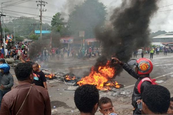Massa membakar ban di pintu masuk Jl. Trikora Wosi di Manokwari, Papua Barat, Senin (19/8/2019), dalam aksi yang merupakan buntut dari peristiwa yang dialami mahasiswa asal Papua di Surabaya, Malang dan Semarang. - Antara