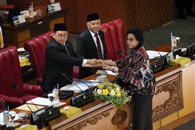 Menteri Keuangan Sri Mulyani Indrawati (kanan) memberikan draft tanggapan pemerintah kepada Ketua Rapat Paripurna Fadli Zon (kiri) didampingi Wakil Ketua DPR Agus Hermanto (tengah) pada Rapat Paripurna DPR di Kompleks Parlemen, Senayan, Jakarta, Selasa (11/6/2019). - ANTARA/Indrianto Eko Suwarso