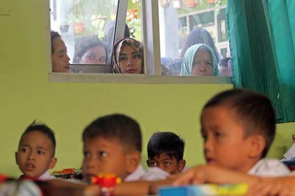 Ilustrasi: Orang tua murid mengawasi anaknya yang menimba ilmu tingkat sekolah dasar. - Antara/Yulius Satria Wijaya