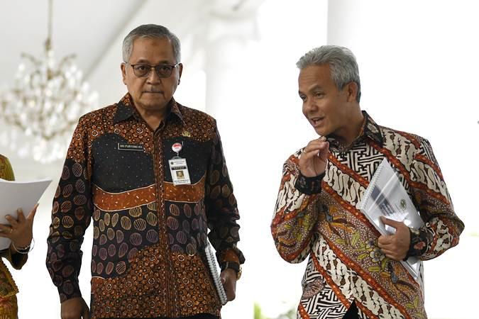 Gubernur Jawa Tengah Ganjar Pranowo (kanan) berbincang dengan Sekda Jawa Tengah Sri Puryono usai mengikuti rapat terbatas tentang percepatan pembangunan di Istana Bogor, Jawa Barat, Selasa (9/7/2019). - ANTARA/Puspa Perwitasari