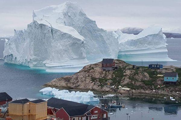 Sebuah gunung es raksasa terlihat di dekat Desa Innaarsuit, Greenland, Kamis (12/7). - Magnus Kristensen via Reuters