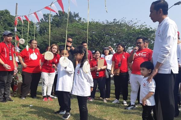 Presiden Joko Widodo dan cucunya Jan Ethes menyaksikan lomba dalam rangka HUT Kemerdekaan 74 RI di Istana Kepresidenan Bogor, Jawa Barat (4/8/2019) - Bisnis/Yodie Hardiyan