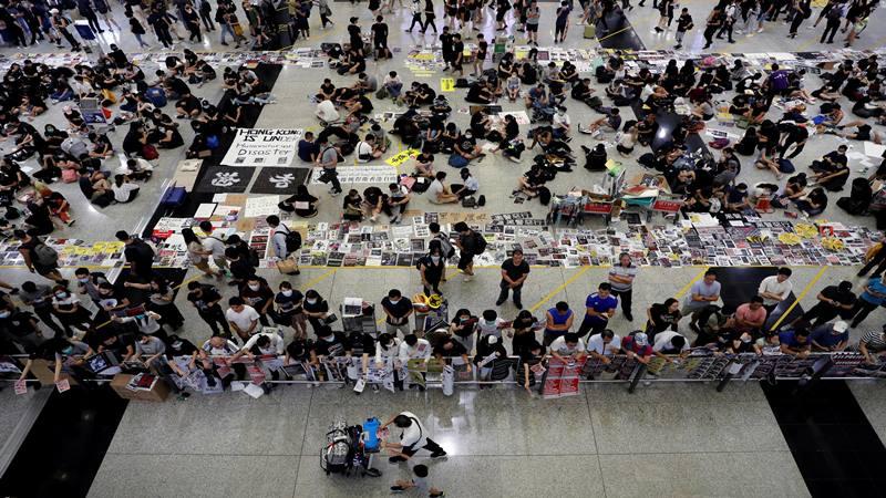 Para pemrotes RUU Anti-Ekstradisi membagikan selebaran kepada para penumpang selama demonstrasi massa di bandara internasional Hong Kong, di Hong Kong, China, 13 Agustus 2019. - Reuters