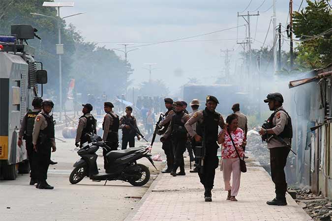 Petugas kepolisian mengevakuasi seorang warga saat melakukan penjagaan aksi di Mimika, Papua, Rabu (21/8).  Antara - Sevianto Pakiding