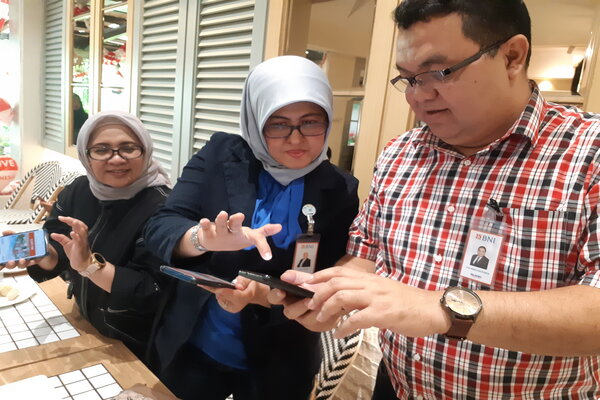 Pemimpin Consumer Banking BNI Wilayah Palembang, Kartika Dewi Palupi (kiri) didampingi Pemimpin Kelompok Kinerja Bisnis & Pengelolaan Jaringan BNI Kanwil Palembang, Yudi Indra A (kanan), menunjukkan pengajuan KPR melalui aplikasi mobile banking BNI. - Bisnis/Dinda Wulandari