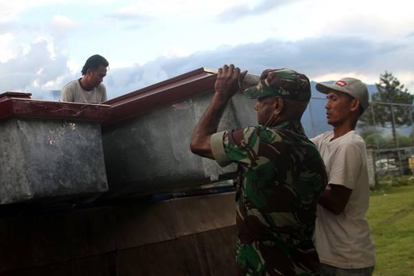 Anggota TNI dibantu warga mempersiapkan peti jenazah untuk korban penembakan Kelompok Kriminal Bersenjata (KKB) di Wamena, Papua, Selasa (4/12/2018). Sebanyak 31 karyawan PT Istika Karya diduga tewas ditembak oleh KKB saat melakukan pengerjaan jalur Trans Papua di Kali Yigi dan Kali Aurak Distrik Yigi, Kabupaten Nduga, Papua pada 2 Desember lalu. - Antara
