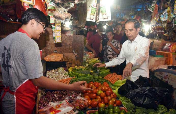 Presiden Joko Widodo (kanan) berdialog dengan pedagang saat mengunjungi Pasar Minggu, Jakarta, Jumat (22/2/2019). Dalam kesempatan itu Presiden juga berbelanja sekaligus memantau harga-harga sembako. - ANTARA/Akbar Nugroho Gumay