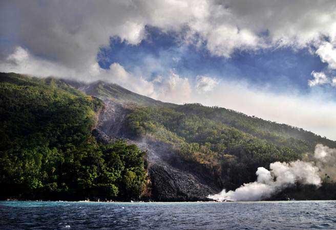 Guguran material vulkanik gunung Karangetang yang jatuh ke laut diamati dari sisi Barat Pulau Siau, Kabupaten Kepulauan Sitaro, Sulawesi Utara, Minggu (10/2/2019). - ANTARA/Adwit B Pramono