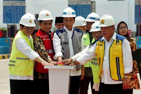 Presiden Joko Widodo (tengah) didampingi Sekretaris Kabinet Kerja Pramono Anung (kiri), Menteri PUPR Basuki Hadimuljono (kanan), Menteri BUMN Rini Soemarno (kedua kanan) dan Wakil Gubernur Jawa Tengah Taj Yasin (kedua kiri) menekan tombol saat peresmian jalan tol Pejagan-Pemalang di Gate Tol Tegal, Kalimati, Kabupaten Tegal, Jawa Tengah, Jumat (9/11/2018). - ANTARA/Oky Lukmansyah