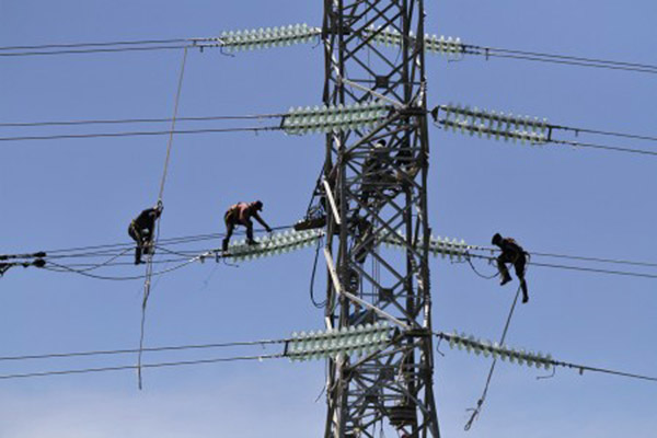 Pekerja memasang jaringan kabel ke tower milik PT PLN yang akan dialiri listrik dari PLTU IPP 3 Kendari, di Desa Pousu Jaya, Konda, Konawe Selatan, Sulawesi Tenggara, Rabu (7/11/2018). - Antara/Jojon