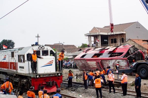 Sejumlah petugas mengevakuasi bus yang tertabrak kereta api Argo Parahyangan KA-32 jurusan Gambir - Bandung di Warung Bambu, Karawang, Jawa Barat, Senin (26/08/2019). Kecelakaan tersebut terjadi akibat bus dengan nomor polisi T 7915 DC mogok di tengah perlintasan kereta api. - ANTARA FOTO/M Ibnu Chazar
