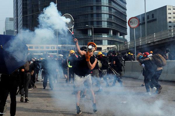 Para pemrotes RUU Anti-ekstradisi menggunakan raket tenis untuk memukul tabung gas air mata saat pawai menuntut demokrasi dan reformasi politik di Teluk Kowloon, Hong Kong, pada Sabtu (24/8/2019). - Reuters/Tyrone Siu