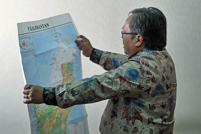 Menteri PPN/Kepala Badan Perencanaan Pembangunan Nasional Bambang Brodjonegoro mengamati peta Pulau Kalimantan di sela-sela wawancara tentang rencana pemindahan lokasi ibu kota, di Kantor Kementerian PPN, Jakarta, Selasa (30/7/2019). - ANTARA/Wahyu Putro A