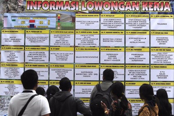 Sejumlah pencari kerja mengamati pengumuman lowongan kerja saat kegiatan bursa kerja di kawasan Lumintang, Denpasar, Bali, Selasa (9/7/2019). Bursa kerja yang diikuti 40 perusahaan yang menyediakan sekitar 1.000 lowongan pekerjaan tersebut diselenggarakan untuk menekan angka pengangguran. - ANTARA FOTO/Fikri Yusuf