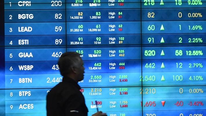 Pekerja melintasi layar monitor bursa saham di Bursa Efek Indonesia (BEI), Jakarta, Selasa (16/4/2019)./ANTARA FOTO - Aditya Pradana Putra