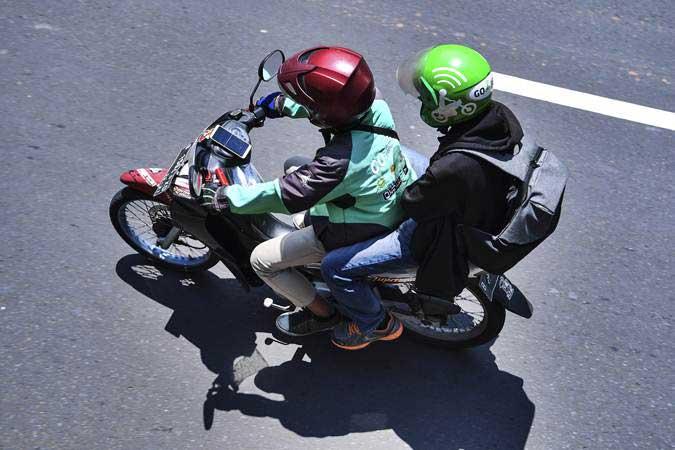 Pengendara sepeda motor menggunakan aplikasi GPS (pelacak jalan) di gawainya saat berkendara di Jalan Rasuna Said, Kuningan, Jakarta, Kamis (7/2/2019). - ANTARA/Hafidz Mubarak A