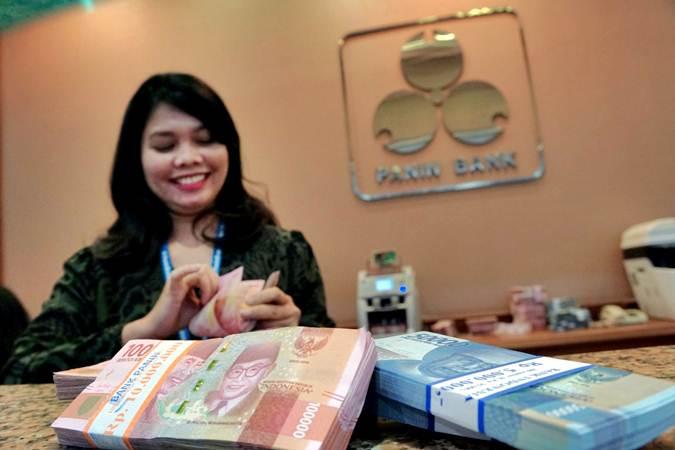 Karyawati menghitung uang rupiah di kantor cabang Bank Panin, di Jakarta, Jumat (5/7/2019). - Bisnis/Himawan L Nugraha