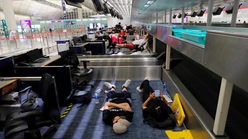 Para pemrotes RUU anti-ekstradisi beristirahat selama demonstrasi massa setelah seorang wanita ditembak mati, di Bandara Internasional Hong Kong, China 12 Agustus 2019. - Reuters
