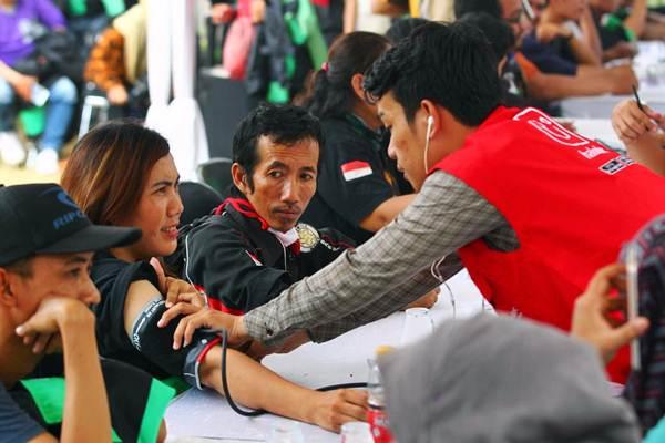 Petugas kesehatan melayani peserta pengobatan gratis bagi 1.000 pengemudi ojek online yang diselenggarakan oleh Halodoc, di Jakarta, Rabu (6/9). - JIBI/Dwi Prasetya