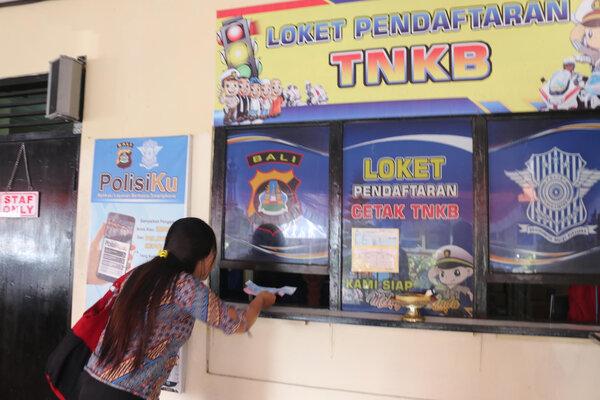 2. Warga sedang mengikuti program pemutihan masal pajak kendaraan bermotor (PKB) dan bea balik nama kendaraan bermotor (BBNKB) di kantor Bapenda Bali Jumat, (30/8/2019). Program pemutihan ini, pada Agustus 2019 sudah sebanyak 70.604 ribu unit kendaraan yang terdaftar dalam program ini dengan dengan pemasukan pajak senilai Rp35 miliar. - Bisnis/Sultan Anshori.