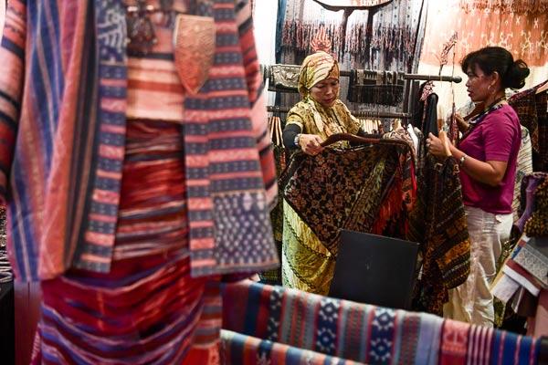 Pengunjung melihat pakaian batik yang dipamerkan pada perhelatan Gelar Batik Nusantara 2019 di Jakarta Convention Center, Jakarta, Rabu (8/5/2019). Acara yang digelar pada 8-12 Mei tersebut sebagai upaya mempromosikan batik dan kerajinannya yang telah menjadi warisan dunia. - foto ANTARA