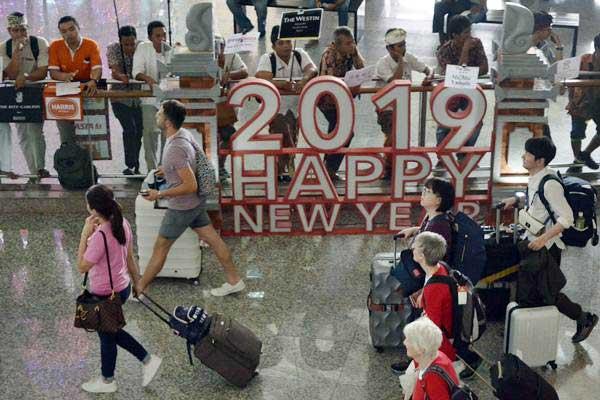 Wisatawan membawa barang milik mereka setibanya di Bandara Internasional I Gusti Ngurah Rai, Bali, Kamis (27/12/2018). - ANTARA/Fikri Yusuf