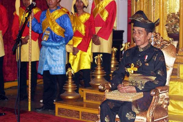 Presiden Joko Widodo mengenakan pakaian adat Melayu Deli saat mengikuti prosesi pemberian gelar adat Melayu Deli, di Istana Maimun, Medan, Sumatera Utara, Minggu (7/10/2018). Kesultanan Deli memberikan gelar adat kepada Presiden Joko Widodo