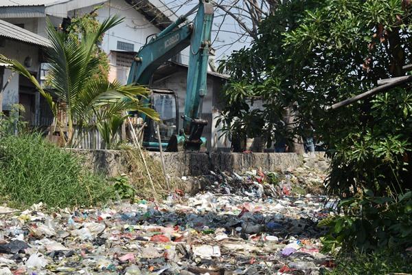 Satu unit alat berat membersihkan sampah plastik yang menutupi Kali Bahagia atau Kali Busa, di Kelurahan Bahagia, Kecamatan Babelan, Bekasi - Antara/Suwandy