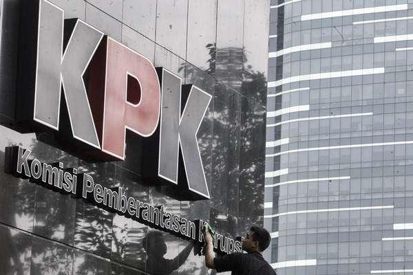 Pekerja membersihkan logo Komisi Pemberantasan Korupsi (KPK) di gedung KPK, Jakart - ANTARA FOTO / Muhammad Adimaja