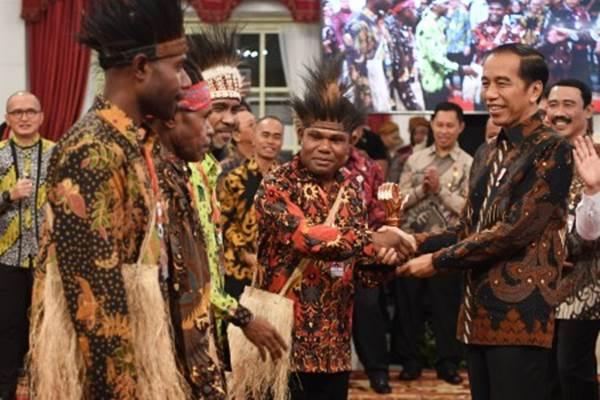 Presiden Joko Widodo (kanan) menyerahkan piala kepada pemenang Festival Gapura Cinta Negeri dari Kepulauan Yapen di Istana Negara Jakarta, Senin (2/9/2019). Presiden bersilaturahmi sekaligus memberikan piala secara simbolis kepada 10 pemenang kategori umum, tiga pemenang kategori lembaga/instansi/perusahaan serta satu pemenang kategori khusus. - ANTARA/Wahyu Putro A