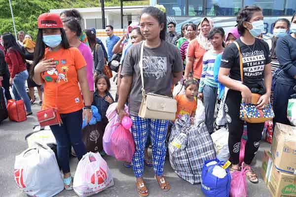 Pekerja Migran Indonesia (PMI) menunggu pendataan oleh petugas BP3TKI saat tiba di Pos Lintas Batas Negara (PLBN) Entikong, Kabupaten Sanggau, Kalimantan Barat, Minggu (27/5/2018). - ANTARA/Reza Novriandi