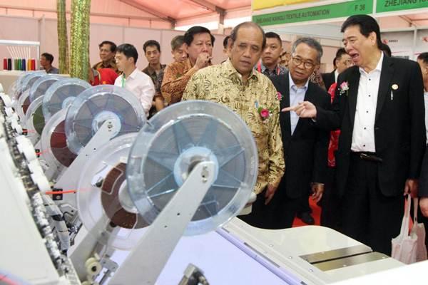 Direktur Industri Tekstil, Kulit, Alas Kaki dan Aneka Kementerian Perindustrian Muhdori (tengah) bersama Ketua Umum Asosiasi Pertekstilan Indonesia (API) Ade Sudrajat (kedua kanan) mengamati mesin tekstil, seusai membuka pameran Indo Intertex 2018, di JIExpo, Kemayoran, Jakarta, Rabu (4/4/2018). - JIBI/Endang Muchtar