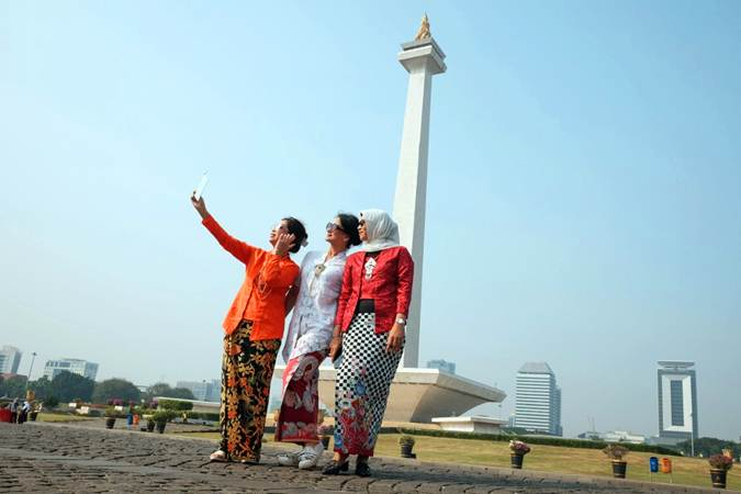 Anggota komunitas gerakan nasional SelasaBerkebaya berswafoto di lapangan Monumen Nasional (Monas), Jakarta, Selasa (2/7/2019). - Bisnis/Felix Jody Kinarwan