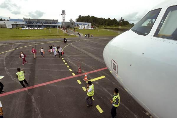 Penumpang maskapai Citilink dengan rute Silangit-Halim Perdanakusuma Jakarta bergegas memasuki pesawat di Bandara Internasional Silangit, Tapanuli Utara, Sumut, Senin (11/12). - ANTARA/Andika Wahyu