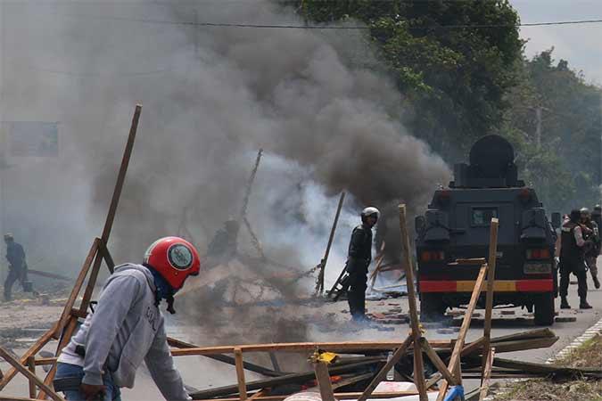 Petugas kepolisian dan TNI melakukan penjagaan saat massa aksi menutup jalan di Mimika, Papua, Rabu (21/8). Antara - Sevianto Pakiding