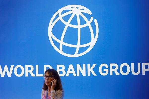 Peserta berdiri di dekat logo Bank Dunia dalam rangkaian Pertemuan IMF  World Bank Group 2018, di Nusa Dua, Bali, Jumat (12/10/2018). - Reuters/Johannes P. Christo